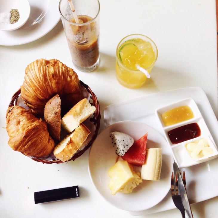 Bữa sáng 75k với bánh mì, croissant, nước cam chanh, cafe, hoa quả, các loại mứt và bơ.