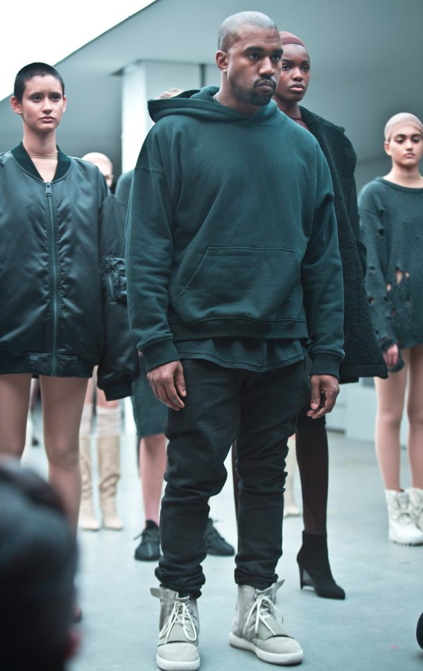 Kanye West appears with models during the showing of his Yeezy Boost shoe line for Adidas on Thursday, Feb. 12, 2015, during Fashion Week in New York. (AP Photo/Bebeto Matthews)